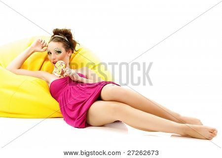 woman beautiful make-up young licks candy on yellow sofa isolated on white background