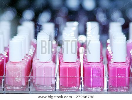 The image of raws of bottles with varnish nails. Focus is under the central bottles