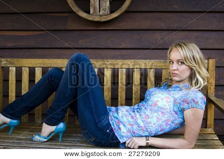 young happy girl lying on a bench seat