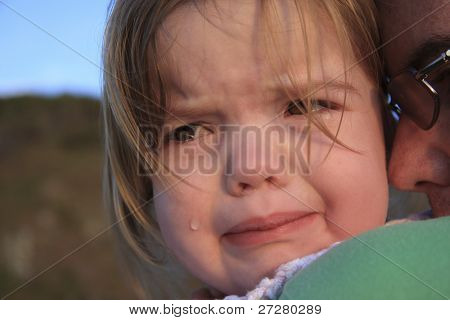 young girl crying on her father's shoulder