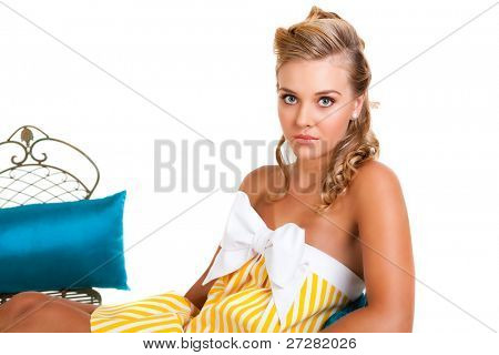 Portrait of a young woman in a yellow dress. Sitting on a chair with a blue cushion Horizontal shot. Isolated on white.
