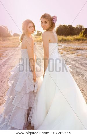 Attractive young bride and bridesmaid in formal attire. They are walking in the country holding hands at sunset.