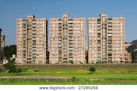 It is beautiful cityscape of apartments with grassland.