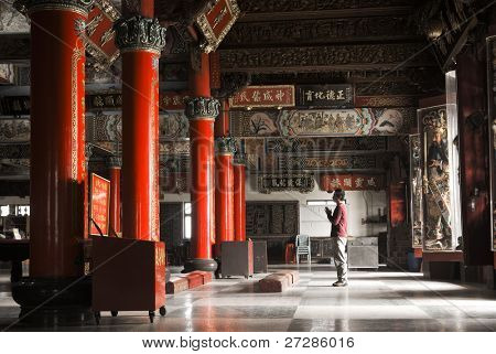 Building interior of temple with one Asian prayer begging and standing.