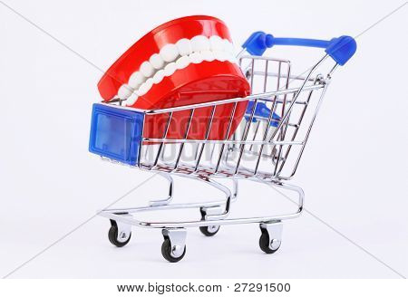 small toy jaw with white teeth in purchasing cart on white background