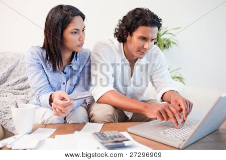 Young couple checking their bank accounts online