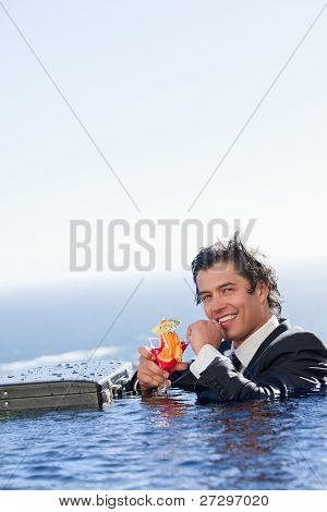 Portrait of a smiling businessman relaxing in a swimming pool with a cocktail in a suit