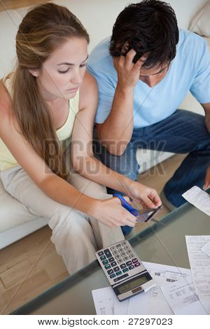 Portrait of a couple cutting their credit card in their living room
