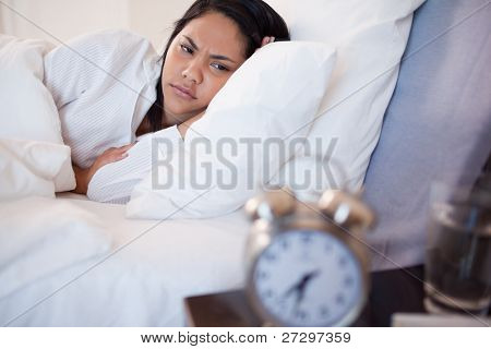 Side view of young woman being woken by alarm clock