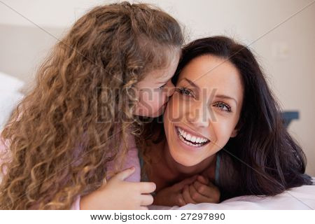 Little daughter giving her mother a kiss on the cheek