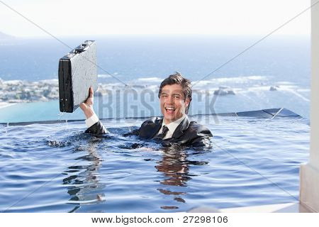 Businessman holding a briefcase in a swimming pool