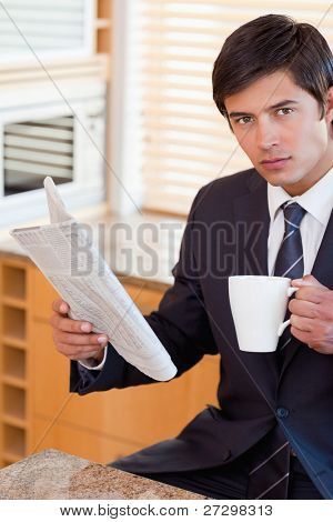 Portrait of a businessman drinking tea while reading a newspaper in his kitchen