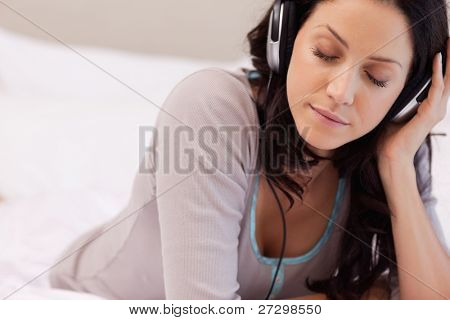 Young woman enjoying music in her bedroom