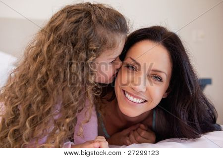 Little daughter giving her young mother a kiss