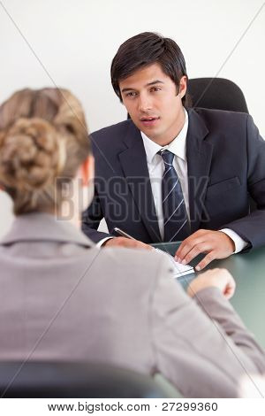 Portrait of a serious manager interviewing a female applicant in his office