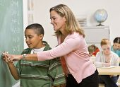 image of student teacher  - Teacher helping student at blackboard - JPG