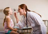 stock photo of doctors office  - Doctor giving girl checkup in doctor office - JPG