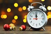 Midnight Clock And Christmas Balls On Wooden Background poster