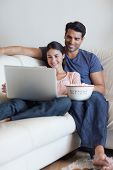 Portrait of a couple watching a movie while eating popcorn with a laptop