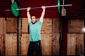 Young Smiling Athlete Doing Some Weightlifting Exercises With Green T-shirt poster