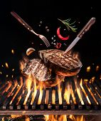 Raw beef steaks with vegetables and spices fly over the blazing grill barbecue fire. Concept of flyi poster