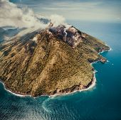 Fog over Indonesia volcano. Aerial drone shot. Amazing overview of Indonesian land surrounded by the poster