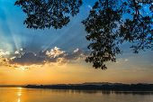River Sunset / Landscape Of Beautiful Sunset On River Colorful Blue Sky With Tree Branch Foreground poster