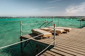 Pier With Chaise Longues In The Sea In Resort. Summer Vacation. View At A Clear Sea With Turquoise W poster