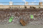 Beach Loungers And Wooden Table, Hanging From A Red Brick Wall poster