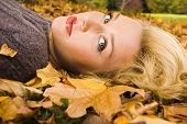 image of country girl  - Young girl lying in the Autumn fall leaves - JPG