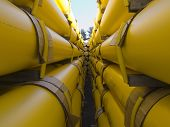stock photo of gas-pipes  - a stack of yellow natural gas pipes in a utility company yard - JPG