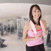 Smiling fit girl holding towel and taking rest in gym.