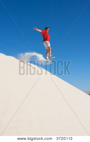 Man In Red Shirt Taking A Leap Off The Top Of White Sand Dune With A Blue Sky