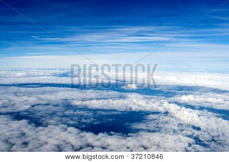 background of clouds. view from the airplane. Top view. continuous carpet of clouds against a blue sky