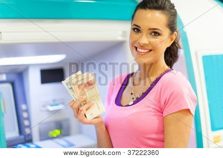 happy young woman withdrawing or depositing cash at an ATM