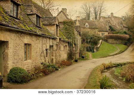 Bibury.Traditional Cotswold cottages in England, UK. Photo in retro style. Paper texture.