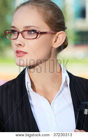 Portrait of a business woman standing in the big city and purposefully looking away.
