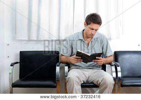 Young man reading book in doctor's waiting room
