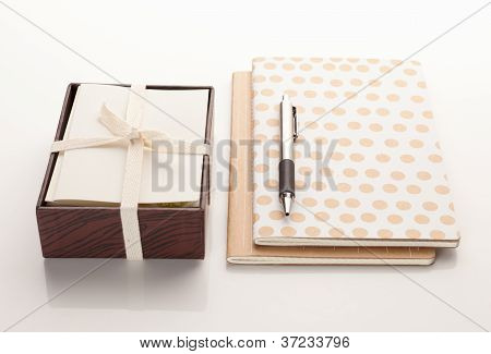 Stationary with notebooks and a pen