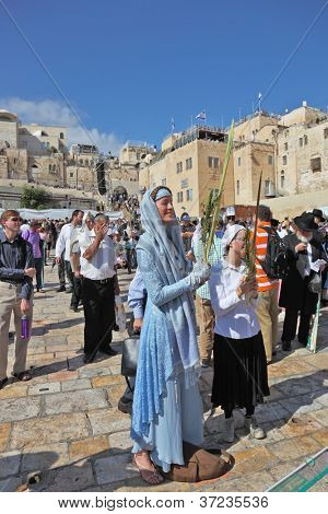 JERUSALEM-OCTOBER 16: The Holy Western Wall of the Temple. A young woman  holds the lulav in hand in front of the Wailing Wall in Sukkot, October 16, 2011 in Jerusalem, Israel
