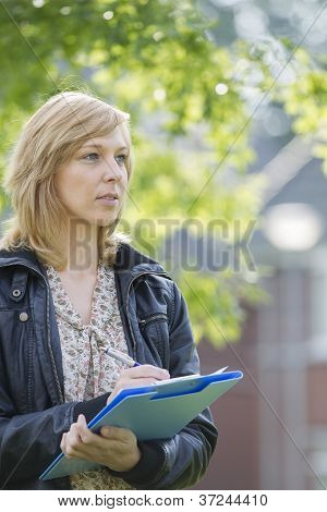 Serious woman with folder and pen outdoors