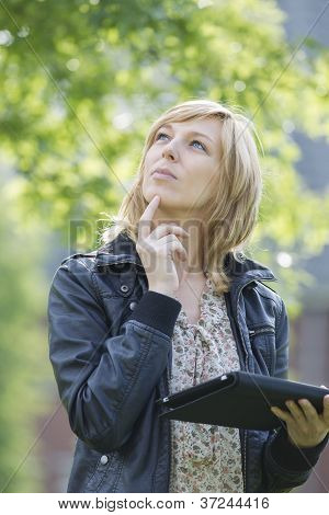 Thoughtful woman with digital tablet looking up