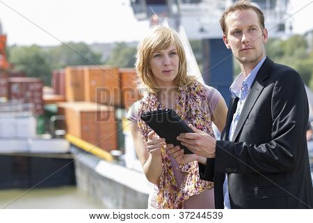Colleagues with digital tablet looking away