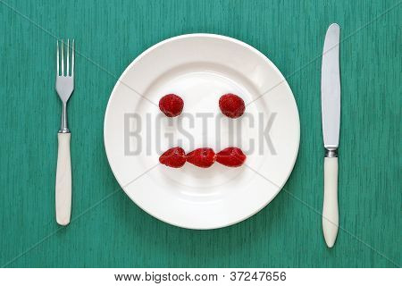 Fork, Knife And Indifferent Face Made Of Strawberries On Plate