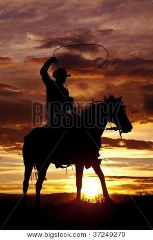 Cowboy Swinging Rope On Horse Side Angle