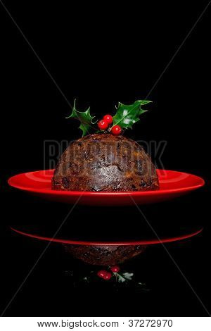 Christmas pudding with holly on top against a black background.