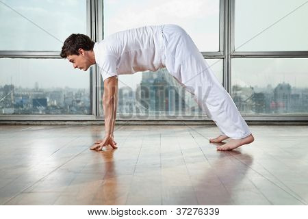 Side view of a young man practicing yoga called Downward Facing Dog at gym