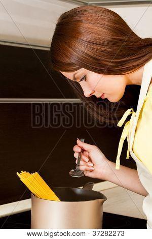 Beautiful woman preparing spaghetti in the kitchen