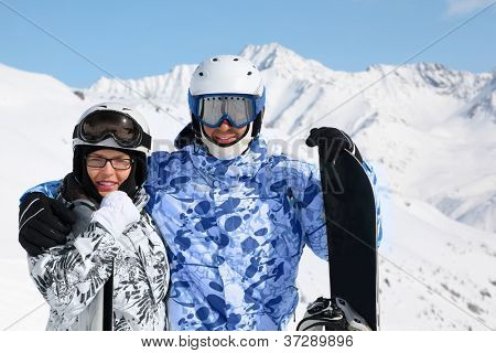 Happy couple in sport suits and helmets stand with snowboard and skis on mountain.