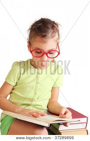 Little girl seat, hold, read book, pose face near stack of books